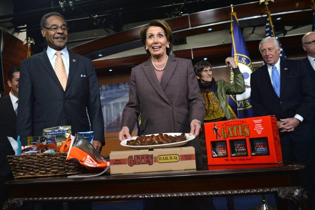 House Minority Leader Nancy Pelosi, D-Calif, holds up a plate of ribs given to her by Rep. Emanuel Cleaver, D-MO, in honor of the San Francisco Giants defeating the Kansas City Royals, in Washington, D.C. on November 18, 2014. UPI/Kevin Dietsch