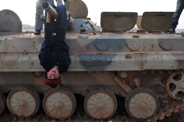 Libyans play on tanks abandoned by the military in Benghazi, Libya on March 2, 2011. Gadhafi warned the West against intervening in the rebellion against his rule. UPI/Mohamaad Hosam