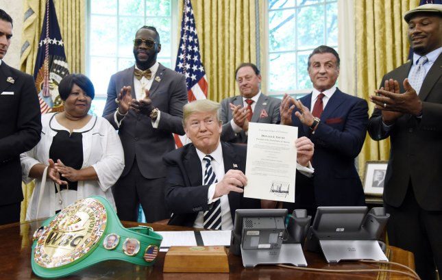 President Donald Trump holds a grant of clemency for boxer Jack Johnson on Thursday in the Oval Office of the White House. Photo by Olivier Douliery/UPI