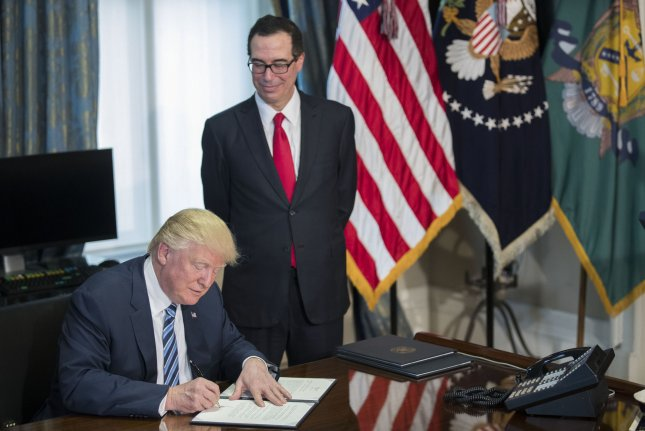 U.S. President Donald J. Trump (L), with Secretary of Treasury Steven Mnuchin (R), participates in a financial services executive order signing in 2017. A treasury report revealed the federal deficit increased to a record level in February. Pool Photo by Shawn Thew/UPI