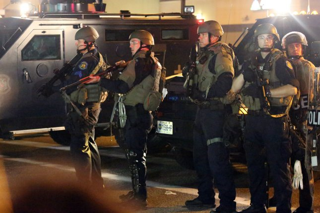 Armed police stand patrol as protesters gather on the streets of Ferguson, Mo., on August 18, 2014. Monday, President Donald Trump signed an executive order restoring local police departments' access to surplus military equipment, like large-caliber firearms, and weaponized aircraft and vehicles. File Photo by Ray Jones/UPI