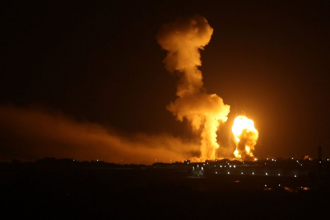 Balls of fire are seen following an Israel airstrike at Rafah in the southern Gaza on Sunday. Israeli aircraft also hit targets near Damascus, killing 6. Photo by Ismael Mohamad/UPI