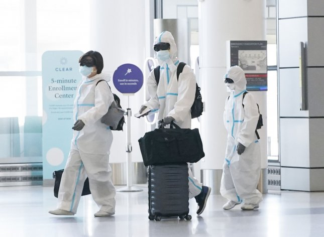 A man, a woman and a child walk through the entrance to terminal 2 at San Francisco International Airport wearing full-body plastic suits, face masks and goggles to prevent catching COVID-19 on Monday. Photo by John Angelillo/UPI