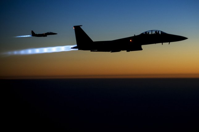 A pair of U.S. Air Force F-15E Strike Eagles fly over northern Iraq early in the morning of September 23, 2014, after conducting airstrikes in Syria. These aircraft were part of a large coalition strike package that was the first to strike ISIL targets in Syria. UPI/Matthew Bruch/USAF