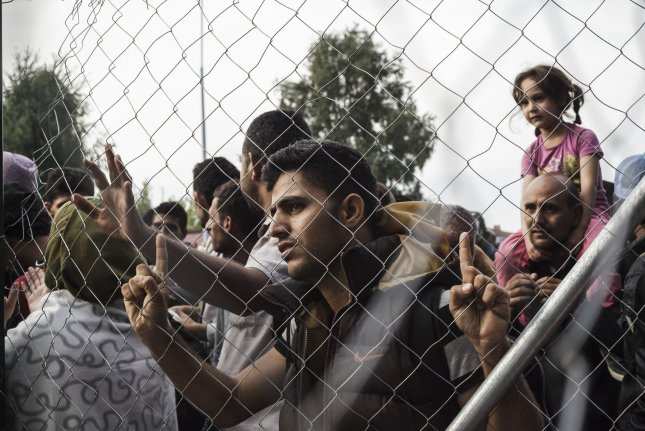 Syrian refugees look through the fence Tuesday at the border between Horgos, Serbia and Roske, Hungary. Hungary sealed the border with a fence and soldiers to stop refugees and migrants, and they also started to arrest those without proper papers. Photo by Achilleas Zavallis/UPI