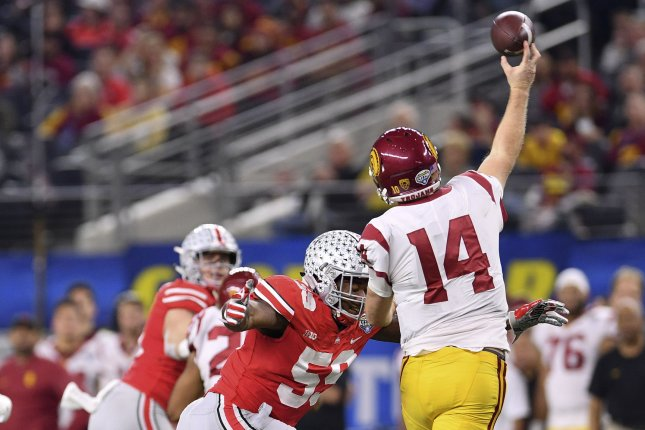 Ohio State Buckeyes defensive lineman Tyquan Lewis #59 pressures USC Trojans quarterback Sam Darnold #14 in the Goodyear Cotton Bowl Classic on Friday at AT&T Stadium in Arlington, Texas. Photo by Shane Roper/UPI