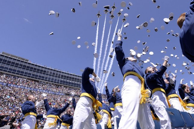 Newly commissioned 2nd Lieutenants celebrate as the U.S. Air Force Thunderbirds fly over the U.S. Air Force Academy Class of 2016 graduation ceremony at Falcon Stadium in Colorado Springs, Colo., on June 2, 2016. Moments after this photograph was taken, one of the F-16s suffered an engine failure and prompted the pilot to eject. Tuesday, the team returned to the skies after a five-day stand-down order. Photo by Mike Kaplan/U.S. Air Force/UPI