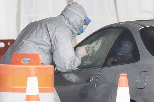 Workers in protective suits check the ID of possible patients when they arrive by car at New York State's first drive-through coronavirus mobile testing center at Glen Island Park in New Rochelle, N.Y., on Friday. Photo by John Angelillo/UPI