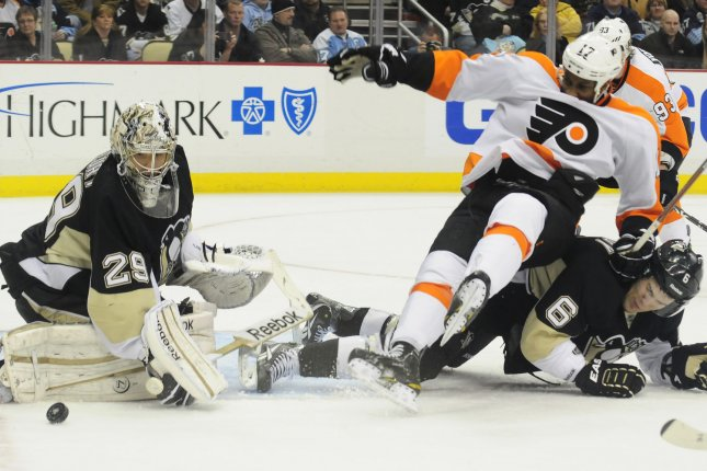 Philadelphia Flyers Wayne Simmonds falls over the back of Pittsburgh Penguins Ben Lovejoy as Pens goalie Marc-Andre Fleury clears the puck away from the goal in the first period at Consol Energy Center in Pittsburgh, Pennsylvania on December 29, 2011. UPI/Archie Carpenter