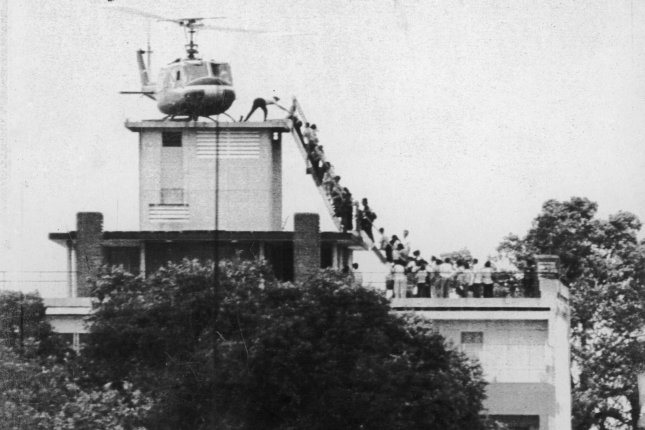 An Air America helicopter crew member helps evacuees up a ladder on the roof of 18 Gia Long Street April 29, 1975 shortly before the city of Saigon fell to advancing North Vietnamese troops. Photo by Hugh Van Es/UPI