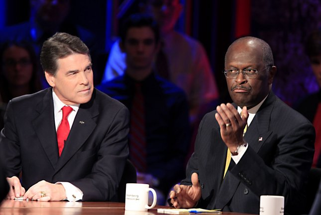 Herman Cain, former chairman and chief executive officer of Godfather's Pizza (R), speaks while Texas Gov. Rick Perry listens during a presidential debate sponsored by Bloomberg and The Washington Post held at Dartmouth College in Hanover, N.H., Oct. 11, 2011. UPI/Melina Mara/Pool
