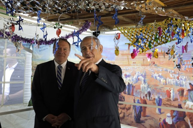 U.S. Secretary of State Mike Pompeo (L) and Israeli Prime Minister Benjamin Netanyahu speak Friday at a sukkah, a traditional shack built for the week-long Jewish holiday of Sukkot, at Netanyahu's residence in Jerusalem. Photo by Sebastian Scheiner/UPI/Pool