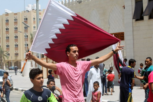 A Palestinian man holds a Qatari flag during a rally in support of Qatar in southern Gaza June 9. The United Arab Emirates rejected a report indicating it hacked Qatari government news and social media websites. File Photo by Ibrahim Khatib/UPI