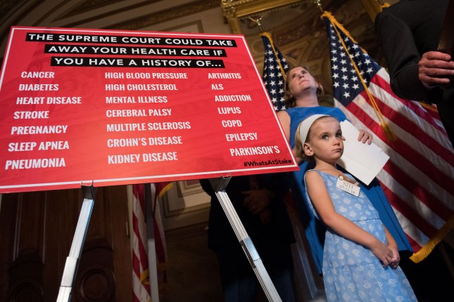 A child born with pre-existing health conditions attends a news conference with Senate Democrats who are critical of Trump administration efforts to alter the U.S. healthcare system, on Capitol Hill on July 11, 2018. File Photo by Kevin Dietsch/UPI