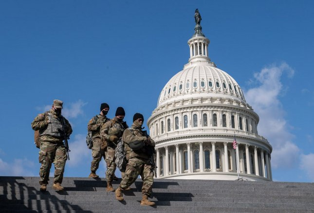 Members of the National Guard walk past the U.S. Capitol in Washington, D.C. on Thursday. The House of Representatives canceled its session today after receiving information about a possible security threat at the Capitol. Photo by Kevin Dietsch/UPI