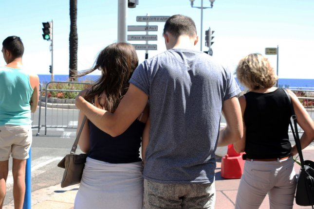 People mourn on the Promenade des Anglais in Nice, France, on Friday. More than 80 people were killed and many more were injured when a truck ran over a crowd of revelers attending the Bastille Day fireworks. Among the injured are three American students from the University of California-Berkeley, and officials said one of the school's students is missing. Photo by Maya Vidon-White/UPI