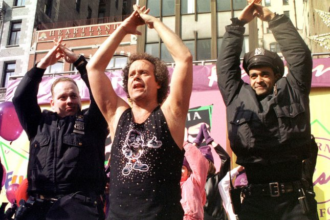Fitness guru Richard Simmons convinces New York Police officers to join in on an impromptu excersise session at a February 10, 2000 press conference. A rep for Simmons denied that he is being held hostage by his maid. File Photo by Ezio Petersen/UPI