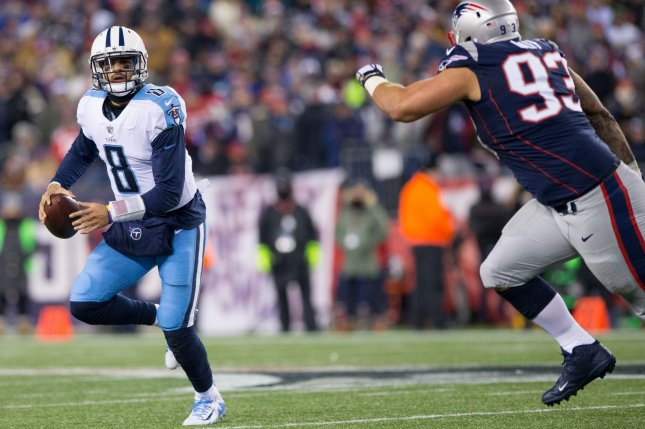 Tennessee Titans quarterback Marcus Mariota (8) is chased by New England Patriots defensive lineman Lawrence Guy (93) as he scrambles in the first quarter of the AFC Divisional Round on January 13 at Gillette Stadium in Foxborough, Massachusetts. Photo by Matthew Healey/UPI