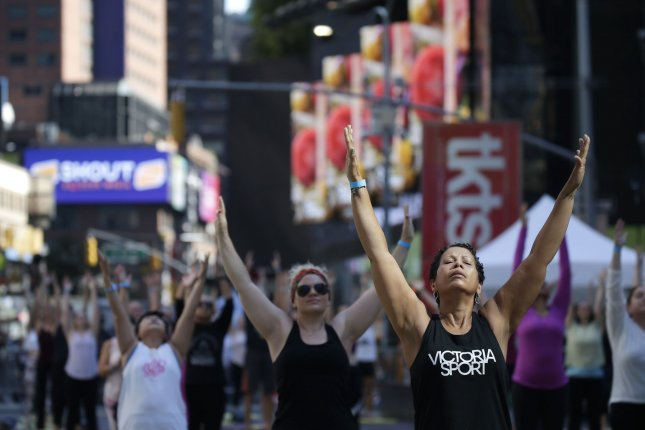 Yogis return to Times Square to participate in Solstice in Times Square: Mind Over Madness Yoga, an annual all-day outdoor yoga event, in New York City on Sunday, June 20, 2021. Photo by John Angelillo/UPI