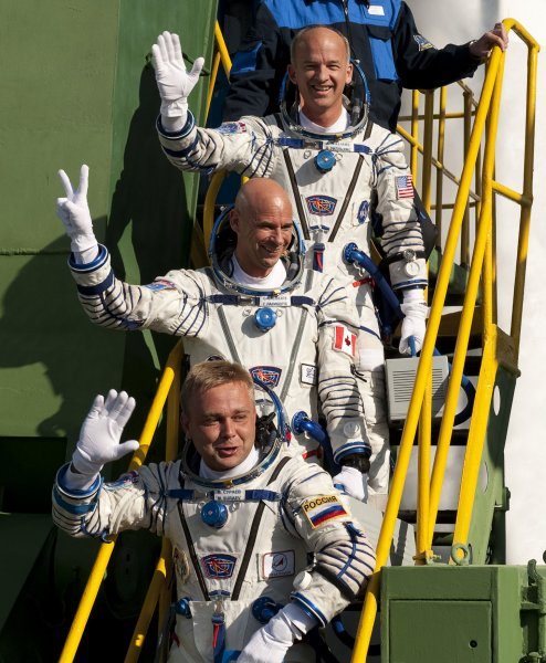 Expedition 21 Flight Engineer Jeffrey N. Williams, top, Spaceflight Participant Guy Laliberte, middle, and Expedition 21 Flight Engineer Maxim Suraev wave farewell from the bottom of the Soyuz launch pad prior shortly before their launch onboard the Soyuz TMA-16 from the Baikonur Cosmodrome in Kazakhstan, Wed., Sept. 30, 2009. UPI/Bill Ingalls/NASA