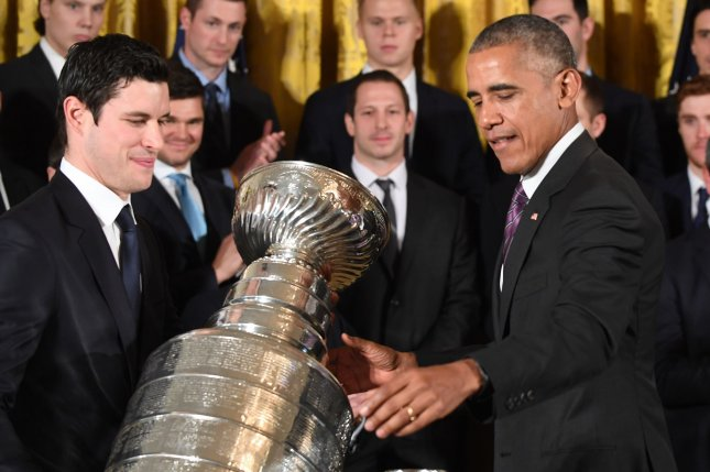 U.S. President Barack Obama helps Pittsburgh Penguins captain Sidney Crosby carry the Stanley Cup as he honors the NHL 2016 Stanley Cup Champions Pittsburgh Penguins in the East Room of the White House in Washington, DC on October 6, 2016. Photo by Pat Benic/UPI