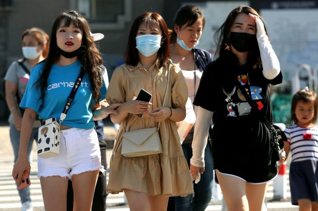Some Chinese continue to wear protective face masks outdoors while others do not after the government lifted the requirement in Beijing on August 24. Mainland China was the original epicenter of the pandemic, announcing the first fatality from the disease on January 15. File Photo by Stephen Shaver/UPI