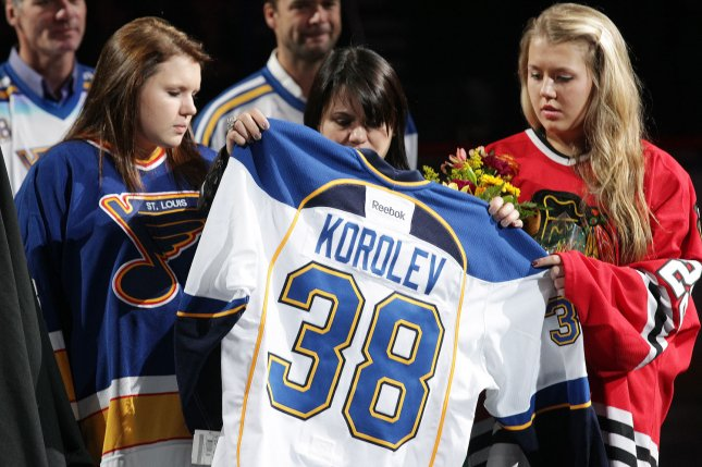 The family of former St. Louis Blues player Igor Korolev hold his jersey during a tribute ceremony before the St. Louis Blues-Chicago Blackhawks hockey game at the Scottrade Center in St. Louis on November 8, 2011. Korolev was among those killed on September 7, 2011, when the plane carrying their KHL team, Lokomotiv Yaroslavl, crashed in Russia. File Photo by Bill Greenblatt/UPI