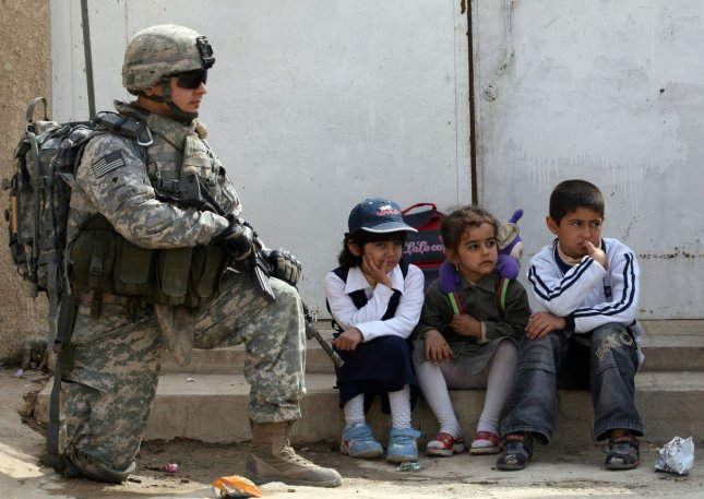 A U.S. soldier visits Iraqi children at the reopening of an elementary school that was reconstructed and repaired from war damages in the Al-Hurriya district north of Baghdad on March 5, 2009. (UPI Photo/Ali Jasim)
