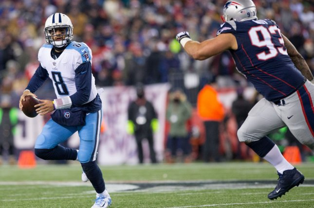 Tennessee Titans quarterback Marcus Mariota (8) is chased by New England Patriots defensive lineman Lawerence Guy (93) as he scrambles in the first quarter of the AFC Divisional round playoff game on January 13 at Gillette Stadium in Foxborough, Mass. Photo by Matthew Healey/UPI