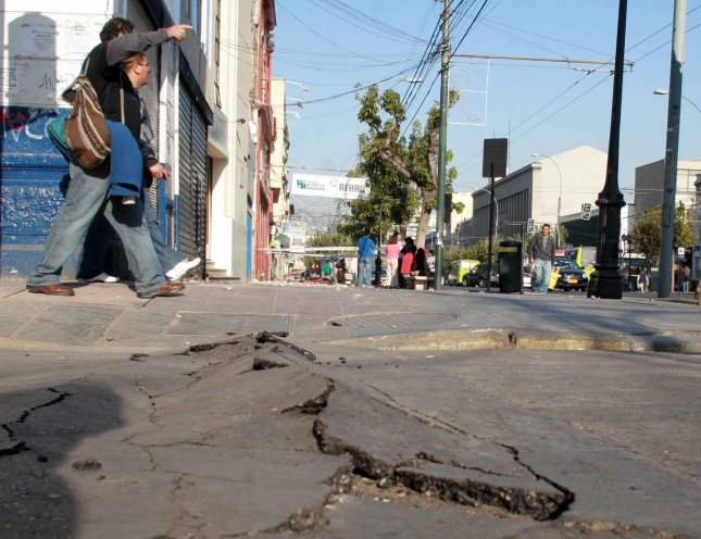 People walk by a crack in the road after an 8.8 magnitude earthquake rocked Chile, in Santiago, Chile, February 27, 2010. At least 147 people are reported dead as the record setting quake has sent tsunami warning all throughout the Pacific. UPI/Sebastián Padilla Rodríguez
