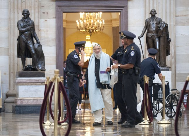 Rabbi Arthur Waskow is arrested as he participates in a group prayer to protest the proposed budget cuts that will threaten programs for the poor and needy on Capitol Hill in Washington on July 28, 2011. The group was arrested after refusing to leave. UPI/Kevin Dietsch