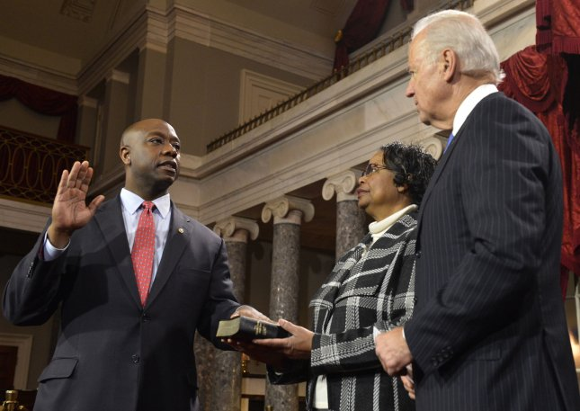 Newly-nominated Sen. Tim Scott (R-SC), (L) places his hand on a Bible held by his mother Frances Scott as he takes part in a re-enactment of his swearing in by Vice President Joe Biden (R), in the Old Senate Chamber at the US Capitol, January 3, 2013, in Washington, DC. The senator was named to replace former Sen. Jim Demint, who resigned, and was previously officially sworn in on the floor of the Senate to begin the 113th Congress. UPI/Mike Theiler