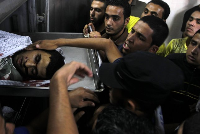 Palestinian relatives mourn near the body of Mohamad AL-reeate, 23, who was killed in an Israeli strike with other two people, at Najar hospital ,Three men were killed and five were wounded in a strike on a group of men, in Rafah in the southern Gaza Strip, Tuesday, Aug. 26, 2014. Israel has agreed to observe an unlimited ceasefire in the Gaza Strip, deal had been reached between Hamas and Israel over a long-term end to seven weeks of fighting. UPI/Ismael Mohamad