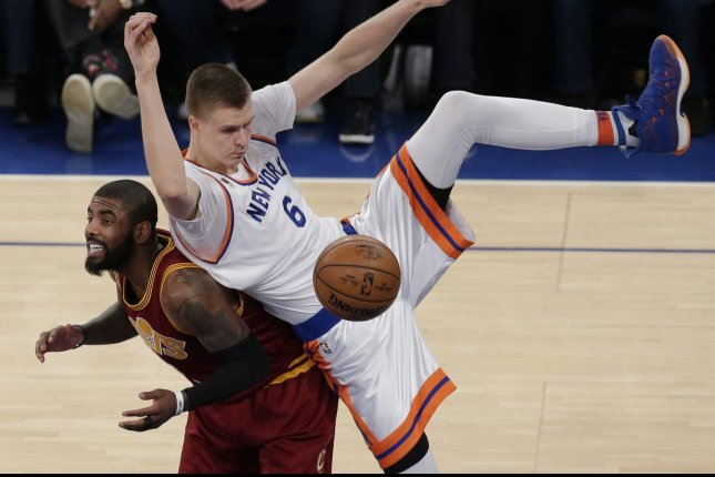 New York Knicks' Kristaps Porzingis lands on Cleveland Cavaliers point guard Kyrie Irving in the first half at Madison Square Garden in New York City on December 7, 2016. The Cavaliers defeated the Knicks 126 to 94. Photo by John Angelillo/UPI