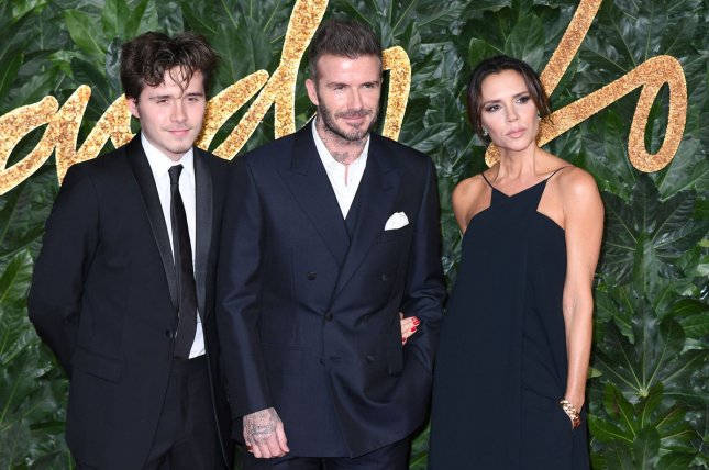 Brooklyn Beckham (L), pictured with David Beckham (C) and Victoria Beckham, shared a photo with Hana Cross on Monday. File Photo by Rune Hellestad/UPI