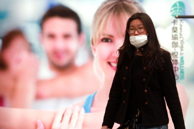 A Chinese shopper walks past a Western health clinic in Beijing, where some say bad air quality, water shortages and desertification pose a threat to development. File Photo by Stephen Shaver/UPI