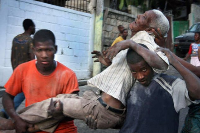 An injured man is carried by survivors of a magnitude-7 earthquake in Port-au-Prince, Haiti, on January 13, 2010. File Photo by Matthew Marek/American Red Cross