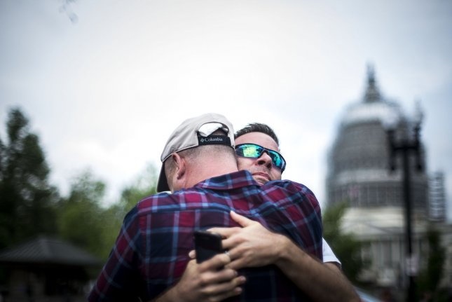 Two men embrace after the Supreme Court ruled 5-4 in favor of gay marriage across the United States at the Supreme Court building in Washington, D.C. on June 26. Monday, the Supreme Court refused to let a Kentucky county clerk continue to deny marriage licenses to same-sex couples based on her religious beliefs. Photo by Gabriella Demczuk/UPI