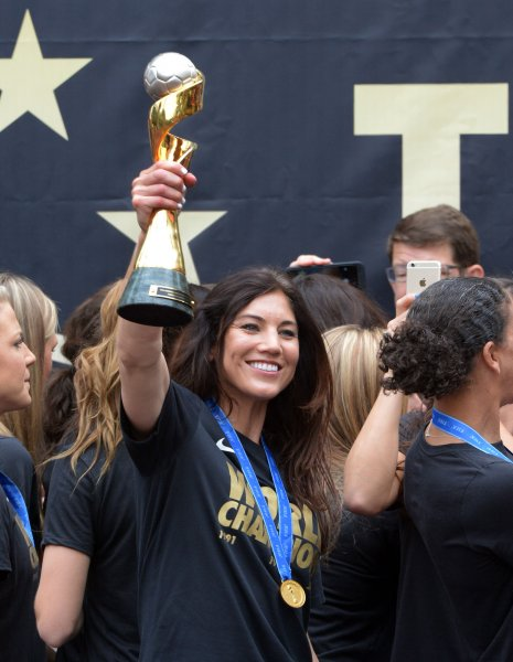 Goal keeper Hope Solo holds the trophy aloft as the USA women's soccer team celebrate their 2015 Women's World Cup victory in Los Angeles on July 7, 2015. Reports show the winning USA female soccer team is paid 40 times less than their losing male counterparts. Photo by Jim Ruymen/UPI