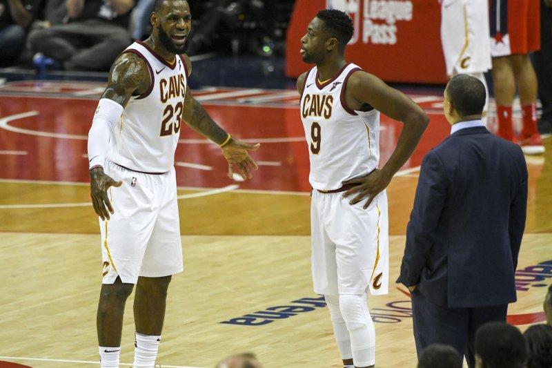 Cleveland Cavaliers forward LeBron James (23) has words with head coach Tyronn Lue as guard Dwyane Wade (9) looks on. Photo by Mark Goldman/UPI