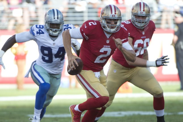 San Francisco 49ers quarterback Blaine Gabbert (2) scrambles away from Dallas Cowboys defensive end Randy Gregory (94) in the second quarter on August 23, 2015 at Levi's Stadium in Santa Clara, California. File photo by Terry Schmitt/UPI