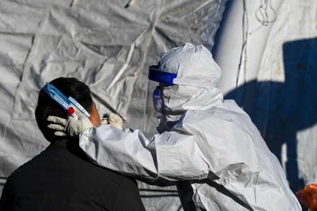 A health worker tests a patient for COVID-19 at a temporary walk-in site in Seoul on December 14. Photo by Thomas Maresca/UPI