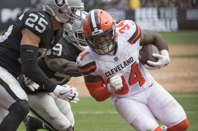 Cleveland Browns running back Carlos Hyde (34) runs for five yards before being pushed out of bounds by Oakland Raiders defender Erik Harris (25) in the third quarter on September 30, 2018 at the Coliseum in Oakland, California. Photo by Terry Schmitt/UPI