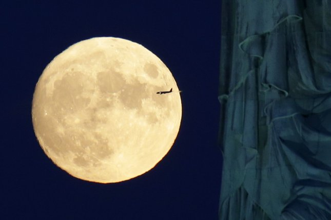An airliner moves in front of a nearly full moon and behind the Statue of Liberty in New York City on Wednesday, seen from Jersey City, N.J. The Harvest Moon will rise late Thursday afternoon. Photo by John Angelillo/UPI