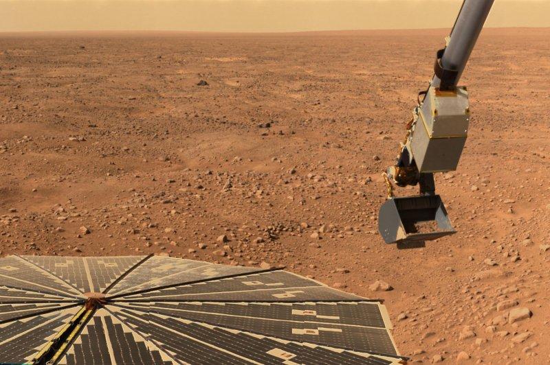 This June 2008 NASA photo shows the robotic arm on the Phoenix Mars lander carrying a scoop of martian soil. (UPI Photo/NASA)