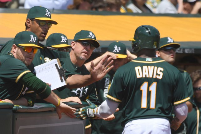 Oakland Athletics' Rajai Davis (11) is congratulated after scoring. File photo by Terry Schmitt/UPI
