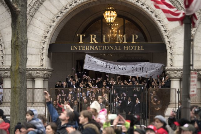 A crowd watches from the Trump International Hotel in Washington, D.C., on January 20, 2017, as President Donald Trump and first lady Melania Trump walk in an inaugural parade. File Photo by Kevin Dietsch/UPI
