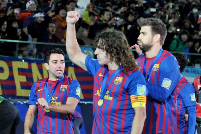 (L-R)Xavi, Carles Puyol, and Gerard Pique parade a winning over Santos FC of Brazil at the final match at the FIFA Club World Cup 2011. (File/UPI/Keizo Mori)
