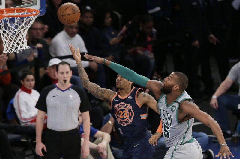 Former Boston Celtics center Greg Monroe defends New York Knicks' Trey Burke in the first half on February 24 at Madison Square Garden in New York City. Photo by John Angelillo/UPI