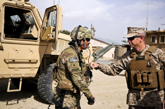 Marine Corps Gen. John R. Allen, commander of NATO and International Security Assistance Force troops in Afghanistan, gives a soldier assigned to Forward Operating Base Ghazni a thump on his body armor as he thanked him for his service and sacrifice on August 15, 2011. UPI/Michael O'Conner/USAF